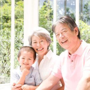 庭先で孫と微笑む祖父と祖母