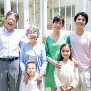 仲良く庭で微笑む3世代の家族