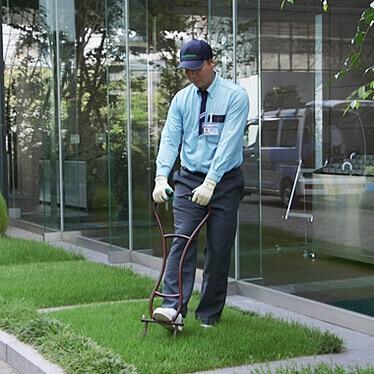 芝生のエアレーション作業を行うトータルグリーンのスタッフ