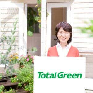 TotalGreenのロゴを掲げる主婦と明るい庭