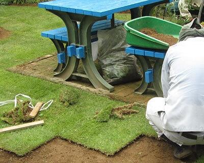 芝生の張り替えを行うトータルグリーンの従業員