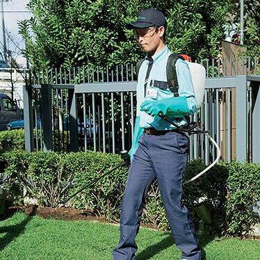 芝生に薬剤をまくトータルグリーンのスタッフ